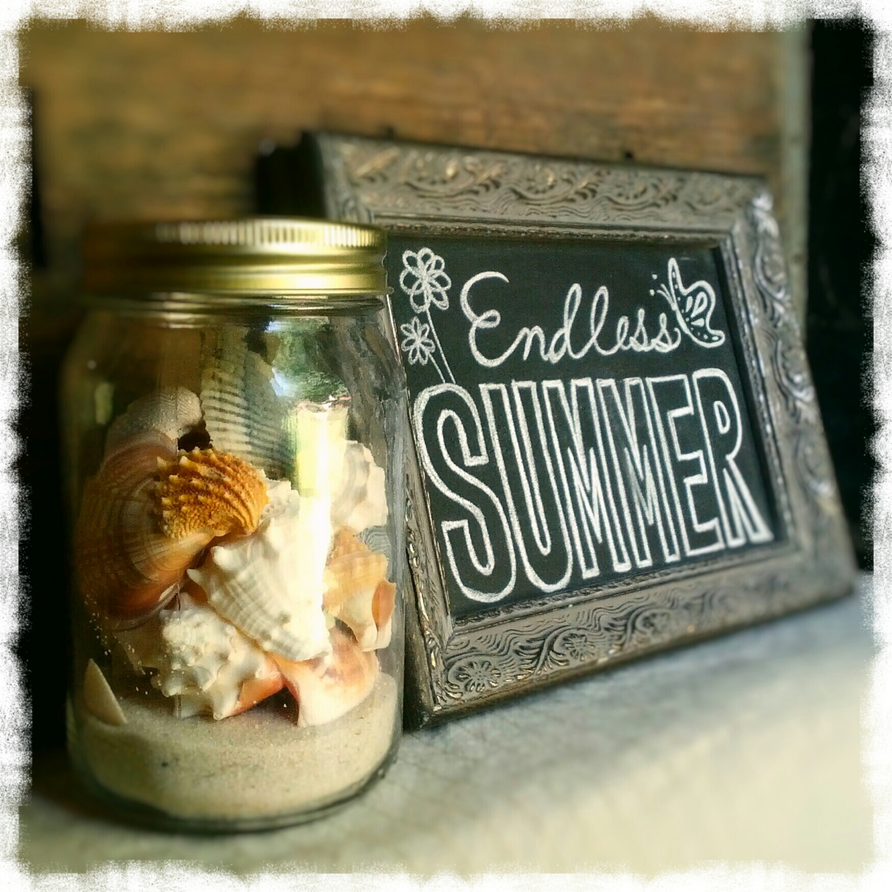 Seashells in a mason jar next to a chalkboard sign that says Endless Summer with flowers and butterflies. Country cottage style beach decor. By Shalom Schultz Designs.