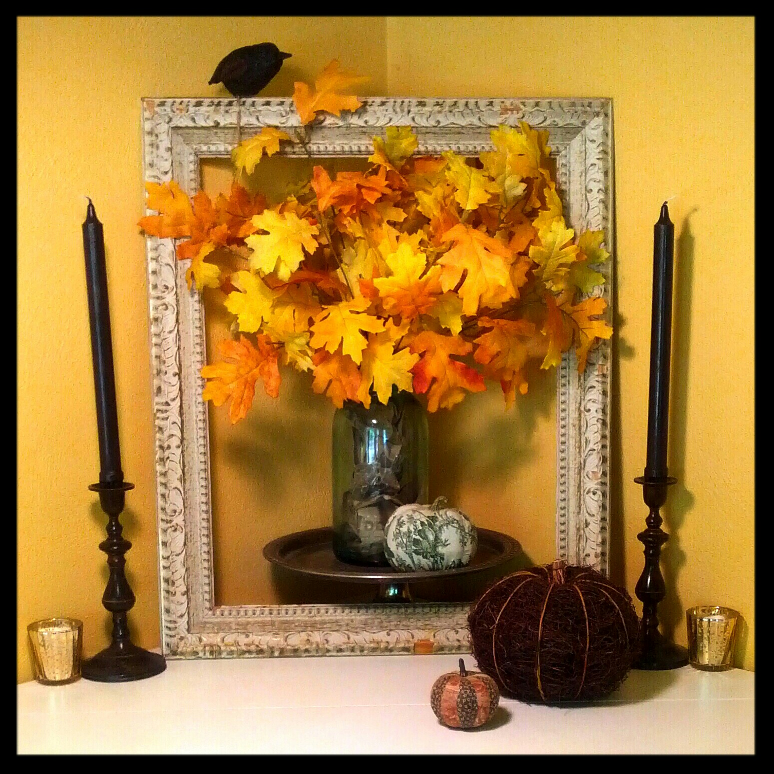 Fall mantel decor with country cottage style vibe, featuring autumn leaves in a mason jar, wicker and handmade fabric pumpkins, mercury glass votives and an antique frame. A black raven bird and dark brown candlesticks with black taper candles add a touch of Halloween fun to this warm & cozy decorating scheme. By Shalom Schultz Designs.