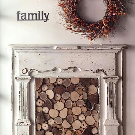 White Fireplace decorated for autumn with a grapevine wreath and a sign that says family. Firewood piled up ready for cooler days. Fall leaves and berries. Family comes first. Country cottage style rustic decor.