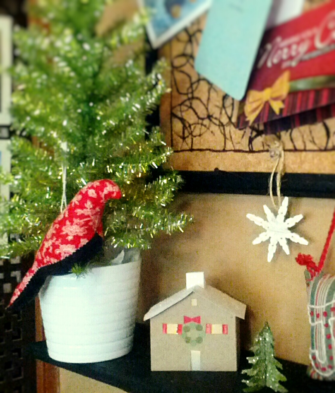 Cottage style Christmas mantel decor with a green tinsel tree in a white pot, mini lighted paper house , a red & black fabric bird, and a wood snowflake ornament. Rustic country style holiday decorating. By Shalom Schultz Designs.