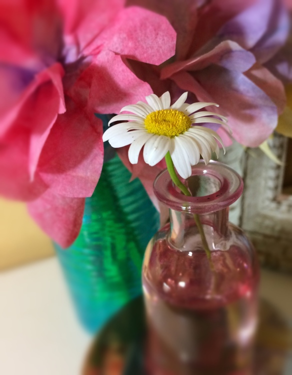 Tiny yellow and white daisy in a small pink glass bottle